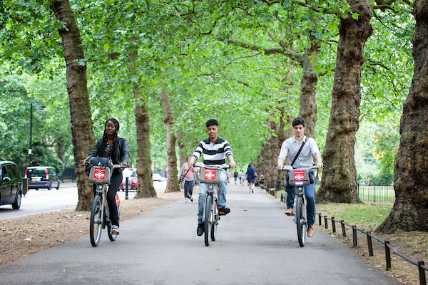 Image of young people cycling in a park