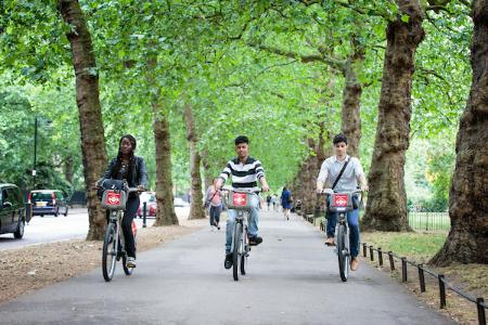 Photo of young people cycling through a park