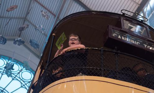 A child aboard a old trolley bus inside the Museum