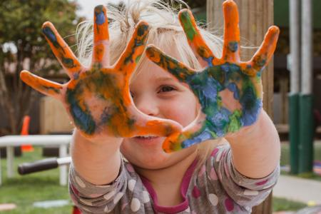Image of a toddler with paint on their palms