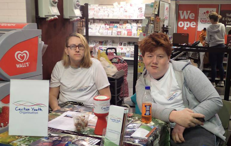 A photo showing two young people representing Caxton Youth Organisation at a stall inside a supermarket