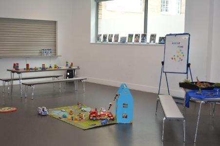 A photo showing the inside of the centre showing toys like building blocks, cars, house and white board.