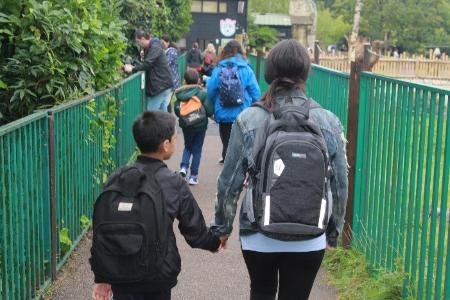 A photo of a mum and her son walking to the centre
