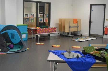 A photo showing the inside of the centre. It shows an indoor tent, a play table and colourful posters.