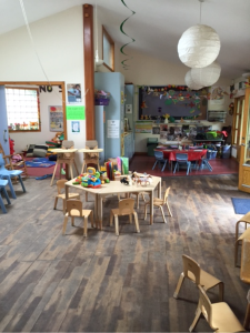 A photo of the main area inside the playhut. Shown are an arrangement of tables and chairs, toys, and colourful decorations