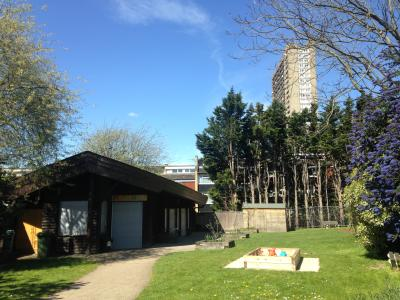 A photo of the outside of the playhut, showing a grassy area and views of Trellick tower