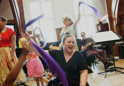 A photo of children and their parents having fun, waving colourful ribbons and playing instruments.