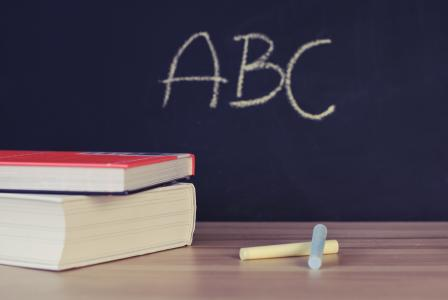 Image of a board with a b c written on it with chalk and books on the side of a table