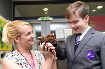 Smiling woman holding a guinea pig, while smiling boy in school uniform strokes it.