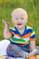Baby covered in paint in long grass.
