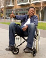 Young man in wheelchair giving a thumbs up hand signal