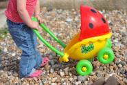 Child on beach with toy buggy