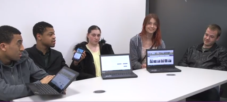 Young people at a desk looking at the Local Offer on laptops and a phone