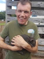 A service user and a piglet at Lindfield Day Opportunities Care Farm
