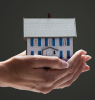 Photo of hands holding a miniature house