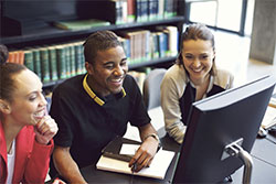 Three young people at looking at computer screen