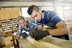 Young person learning woodworking skills during apprenticeship