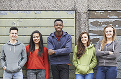 Five young people standing looking directly at the camera casually dressed