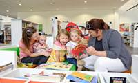 Children, babies and parents or carers looking at picture books