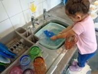 Child learning about independence by washing up after snack time