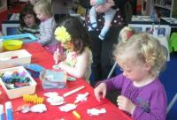 Children sitting at a table taking part in craft activities