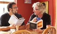 Two men chatting over books