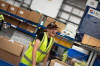 A male Forward2Employment intern smiling at the camera whilst working in a warehouse.