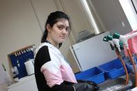 A female Forward2Employment intern, washing up science equipment.