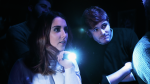 Woman and man looking at something in a dark room with a torch.
