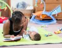 mum reading book with baby