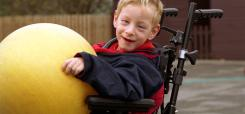 image of disabled child holding a yellow ball