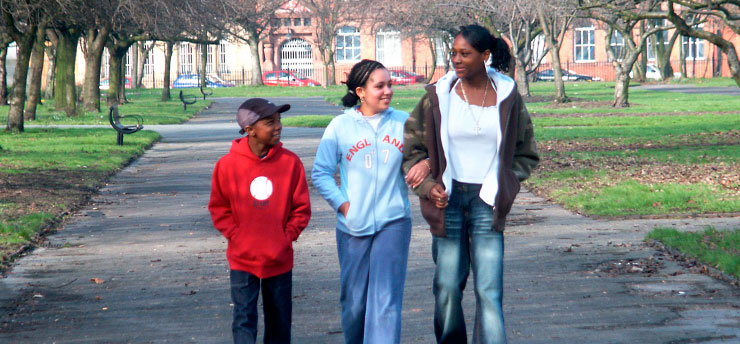 image of three young people walking on a park