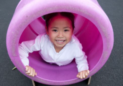 Young Child Playing in pink tunnel