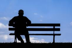 Silhouette of a person sitting on a bench