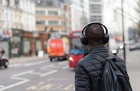 guy with head phones on busy street