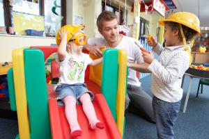 two children playing with male nursery staff member