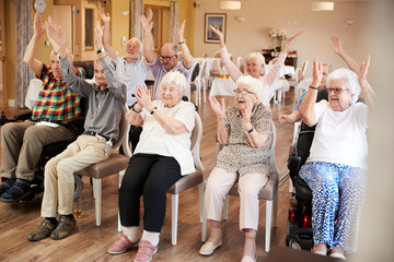 group of old people doing chair exercise