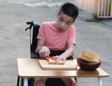 Boy in wheelchair making sandwiches