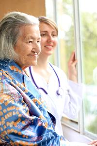 Carer and older lady looking out of a window