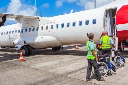 People in wheelchairs boarding a plane