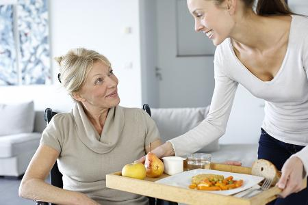 PA with food on tray for lady in wheelchair