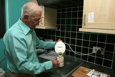 Elderly man with kettle