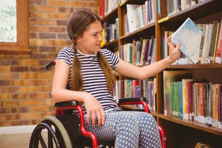 Girl in wheelchair in library