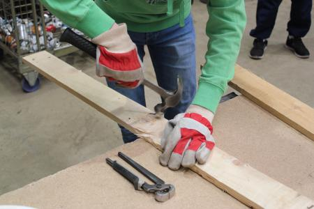 Image of someone taking nails out of a plank with a claw hammer