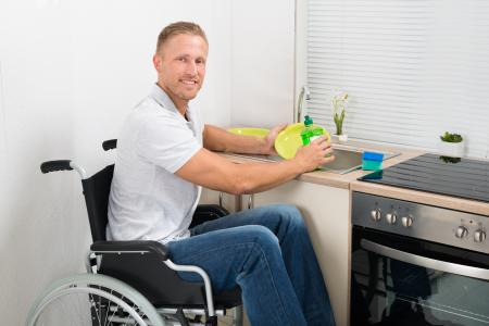 Young man in wheelchair at sink