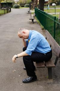 Man on bench with his head in his hands