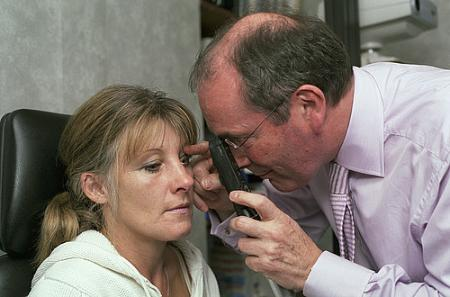 Optician looking at eye