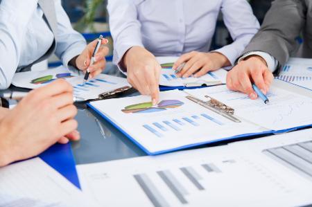 Professionals at a desk discussing a report