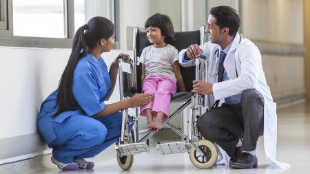 Two health professionals with little girl in wheelchair