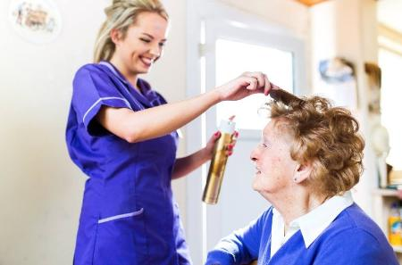 Carer brushing older ladies hair